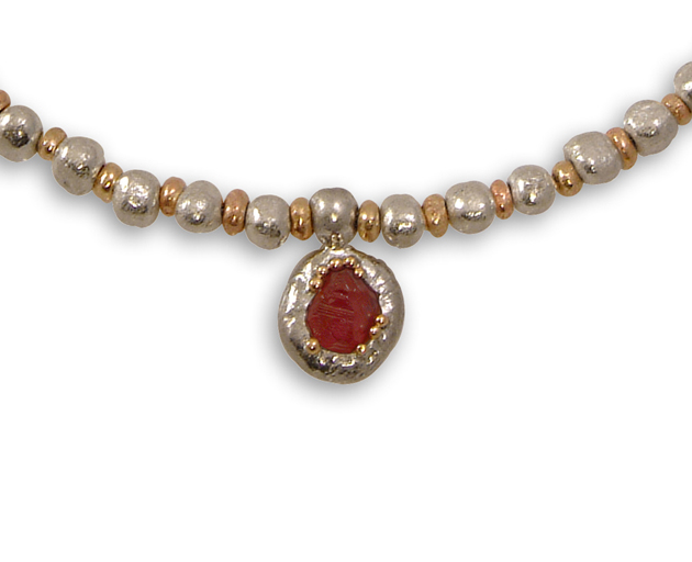 Rough ruby pendant in silver and gold string on a gold and silver nugget bead necklace